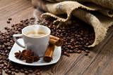 Fototapety Coffee cup with burlap sack of roasted beans on rustic table