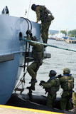 Soldiers marines boarding a ship in a simulated assault.