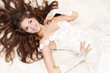 Smiling bride with curly long hair lying over white. High angle