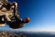 Young man climbing the rock high above mountain range