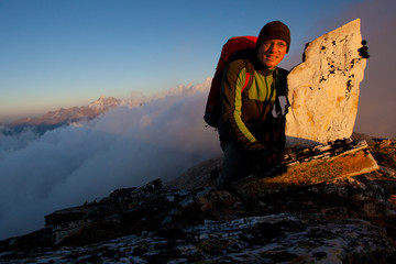 Young man in the Austrian Alps enjoying the sunrise