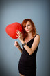 Portrait of beautiful redhead girl with heart balloon.