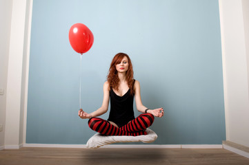 Levitation portrait of red girl with heart balloon.