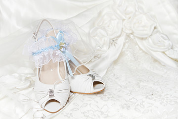 Bride's shoes garter, with blue ribbon, wedding dress. Closeup o
