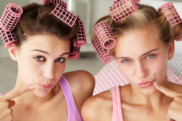 Teenage girls with hair in curlers