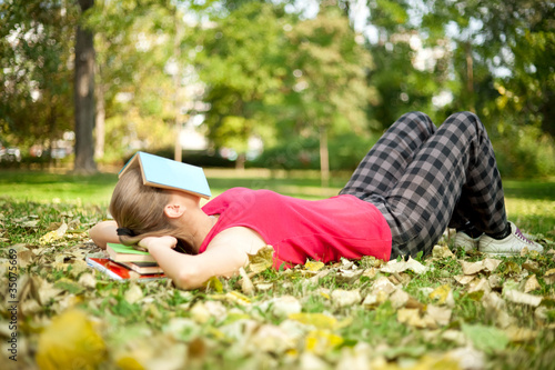 girl relaxing with book on her head