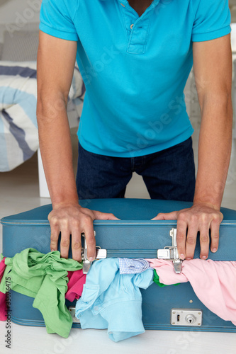 Teenage boy struggling to close suitcase