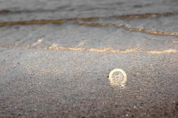Ein Euro Münze im Sand
