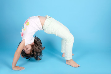 beautiful girl gymnast doing the bridge, studio photo