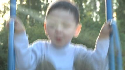 Маленький мальчик катается  на качелях 3