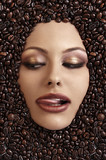 Fototapety close up portrait of a girl's face immersed in coffee beans