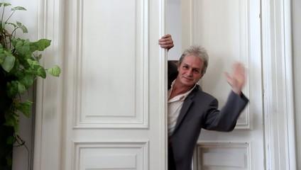 Ein Mann winkt in einer Türe