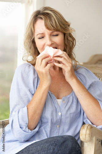 Mid age woman sneezing