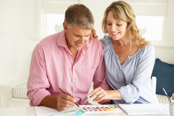 Mid age couple painting with watercolors