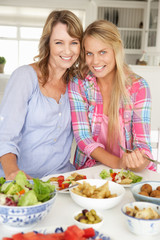 Mother and teenage daughter enjoying meal at home