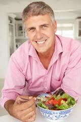 Mid age man eating salad