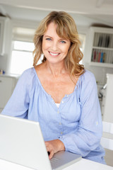 Mid age woman using laptop