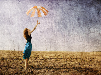 Redhead girl with umbrella at field.