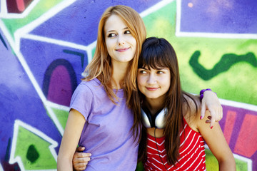 Two girls near graffiti wall.
