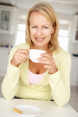 Mid age woman with coffee at home
