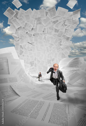 Businessmen running away from wave of documents