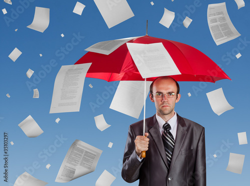 Businessman with red umbrella under falling documents