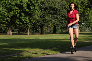 Sexy young woman roller skating in park sunshine