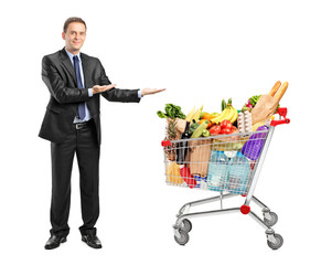 Man in suit gesturing and shopping cart