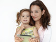 Nice mother and her little girl having fun with touchpad