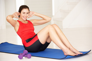 Woman doing sit-ups in home gym