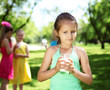Girl drinking milk in the summer park