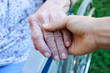 Caregiver holding senior's hand in wheelchair