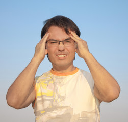 Young man with a headache against blue sky
