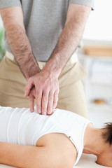 A masseur massages a woman's back