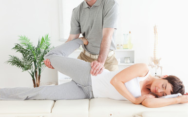 Female customer's leg stretched by chiropractor