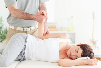 Chiropractor stretches a customer's arm