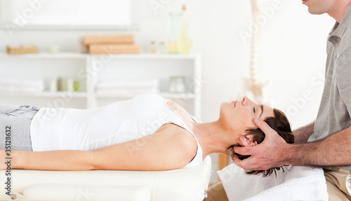canvas print picture Chiropractor stretching a cute woman