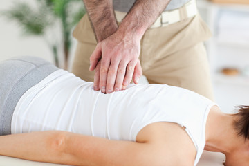 Masseur massages customer's back