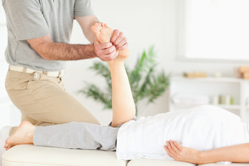 Masseur massaging a customer's foot