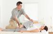 Chiropractor stretching a female customer's leg