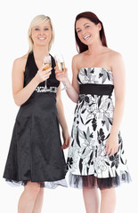 Young women in beautiful dresses with champaign