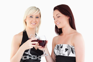 Charming well-dressed women toasting with red wine