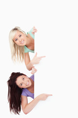 Cute Women peeking around a banner showing copyspace