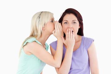 Portrait of a charming woman telling her friend a secret
