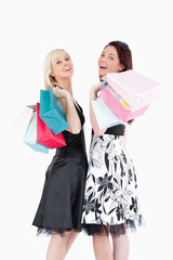 Cheering well-dressed women with shopping bags