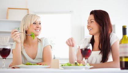 Cheerful women eating salad