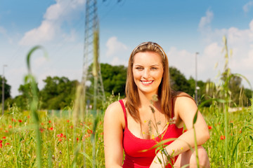 Woman cowering in meadow of field