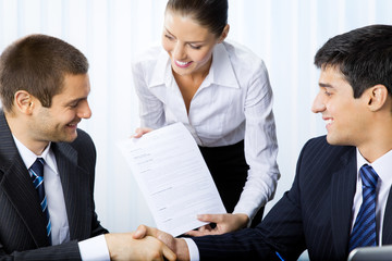 Businesspeople handshaking with document