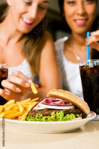 Dwie kobiety jedzenia hamburgera i picia coli