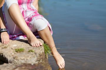 mädchen hält füße ins wasser